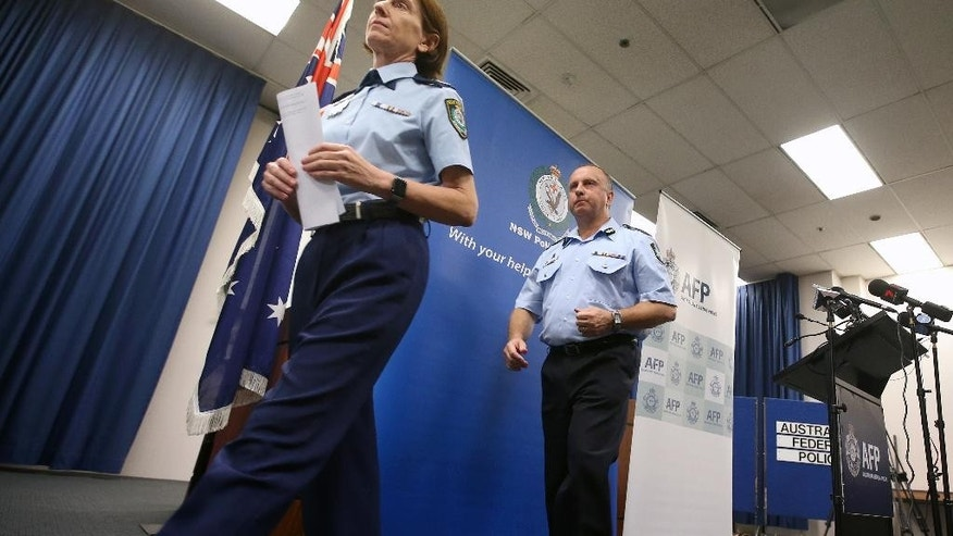 Australian Federal Police Acting Deputy Commissioner Neil Gaughan, right, and New South Wales Deputy Commissioner Catherine Burn depart a news conference where they announced that a teenager has been arrested amid allegations he had been planning to launch a terrorist attack in Sydney, Tuesday, May 17, 2016. The Australian Federal Police said that the 18-year-old would be charged with planning a terrorist attack and preparing to enter a foreign country to engage in hostile activities. (AP Photo/Rick Rycroft)