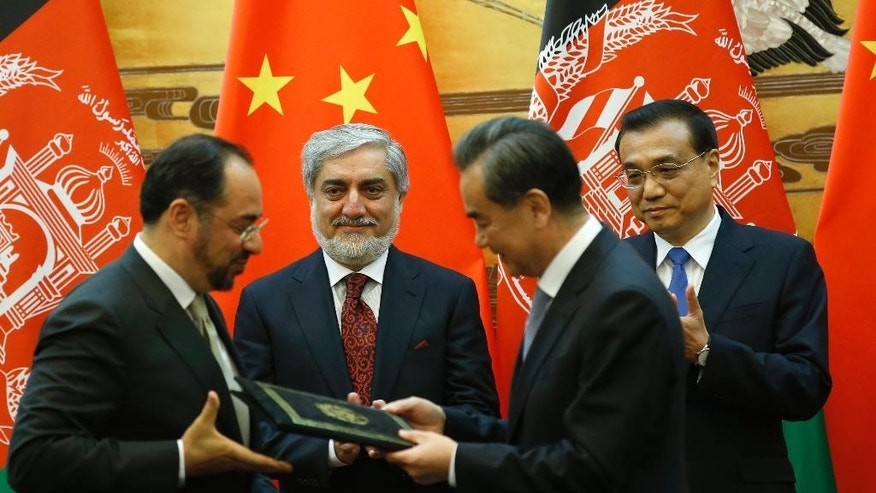 China Premier Li Keqiang,rear right, and Afghanistan Chief Executive Officer Abdullah Abdullah, rear left, applaud while Afghanistan's Foreign Minister Salahuddin Rabbani, left, and China Foreign Minister Wang Yi exchange documents during signing ceremony at the Great Hall of the People in Beijing, China, May 16, 2016. (Kim Kyung-Hoon, Pool Photo via AP)