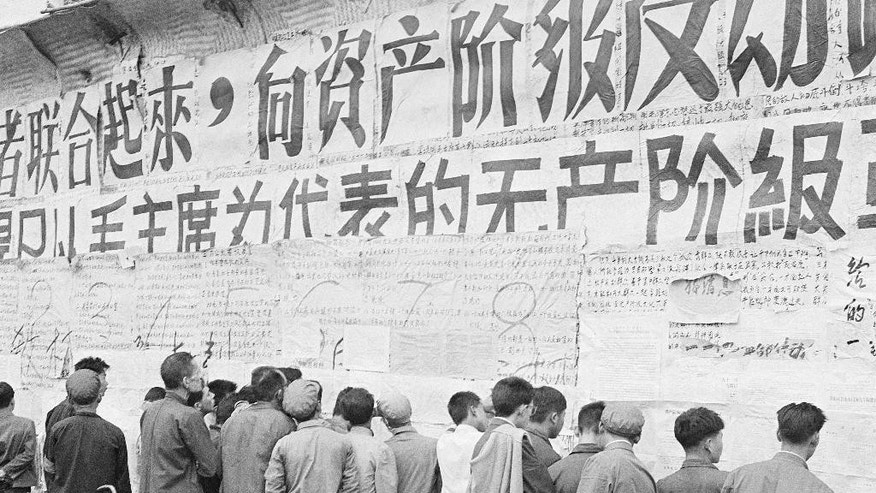 FILE - In this file photo taken Nov. 1, 1967, Chinese citizens view writings and slogans emblazoned on a wall at the height of the decade-long Cultural Revolution initiated a year earlier by Communist Party Chairman Mao Zedong in Beijing. On May 16, 1966, the Communist Party's Politburo produced a document announcing the start of what was formally known as the Great Proletarian Cultural Revolution to pursue class warfare and enlist the population in mass political movements. Launched by leader Mao Zedong, it set off a decade of tumult to revive communist goals and enforce a radical egalitarianism. (AP Photo, File)