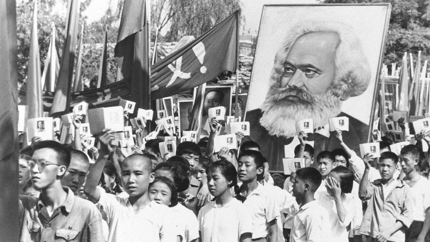 FILE - In this Sept. 14, 1966 file photo, youths are seen at a rally during the height of the Red Guard upheaval waving copies of the collected writings of Communist Party Chairman Mao Zedong, often referred to as Mao's Little Red Book and carrying a poster of Karl Marx. China's official media reaffirmed on Tuesday, May 17, 2016 the Communist Party's longstanding judgment that the Cultural Revolution was a catastrophic mistake after staying silent on Monday's 50th anniversary of the start of the decade-long upheaval. (AP Photo, File)