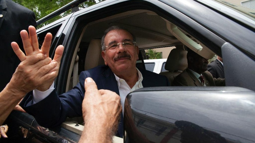 Danilo Medina, current president and presidential candidate for the Dominican Liberation Party, greets supporters after casting his vote during the general elections, in Santo Domingo, Dominican Republic, Sunday, May 15, 2016.  Polls show Medina cruising toward re-election, and he may even win more than 50 percent in Sunday's vote and avoid a runoff. (AP Photo/Tatiana Fernandez)