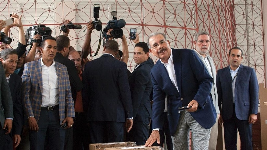 Danilo Medina, current president and presidential candidate for the Dominican Liberation Party, casts his ballot during the general elections, in Santo Domingo, Dominican Republic, Sunday, May 15, 2016.  Polls show Medina cruising toward re-election, and he may even win more than 50 percent in Sunday's vote and avoid a runoff. (AP Photo/Tatiana Fernandez)