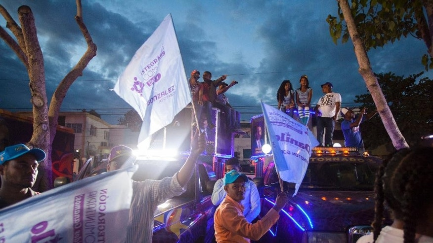 Supporters cheer after President Danilo Medina's speech at a victory rally in Santo Domingo, Dominican Republic, Monday, May 16, 2016. Medina celebrated after winning what appeared to be a resounding re-election victory, with preliminary results showing that he easily had enough votes to avoid a runoff with his closest competitor. (AP Photo/Tatiana Fernandez)