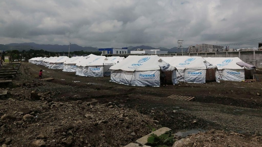 In this May 15, 2016 photo, tents set up for people displaced by last month's earthquake stand in rows at the new bus terminal in Pedernales, Ecuador. A month after the magnitude 7.8 earthquake many Ecuadorians are still struggling. (AP Photo/Dolores Ochoa)