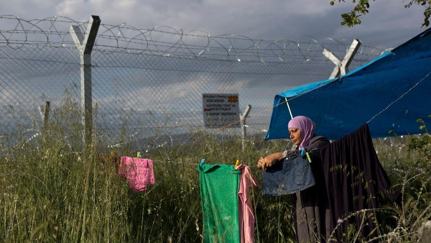 A woman hungs on his laundery near her tent in front of the wired fence that separate Greece and Macedonia at a makeshift refugee camp on the northern Greek border point of Idomeni, Sunday, May 15, 2016. Thousands of stranded refugees and migrants have camped in Idomeni for months after the border was closed. (AP Photo/Petros Giannakouris)