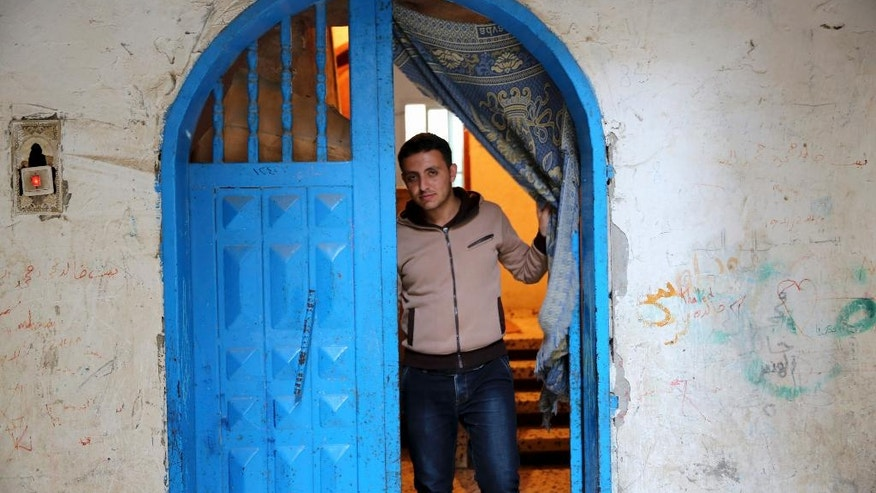 In this Tuesday, May 10, 2016 photo, Mohammed Al-Hissi, 25, who won a  scholarship for a Master's program in physics at the University of Triesta in Italy poses for a photo, at his family house in Gaza City. Gazans who have endured a border blockade by neighboring Egypt and Israel for almost a decade thought they were finally catching a break when Israel slightly eased restrictions on travel from the Hamas-ruled territory in recent months. But now Jordan appears to be emerging as an obstacle, routinely denying transit permits for Gazans and effectively preventing patients, university students and others with business abroad from leaving the coastal territory. (AP Photo/Adel Hana)