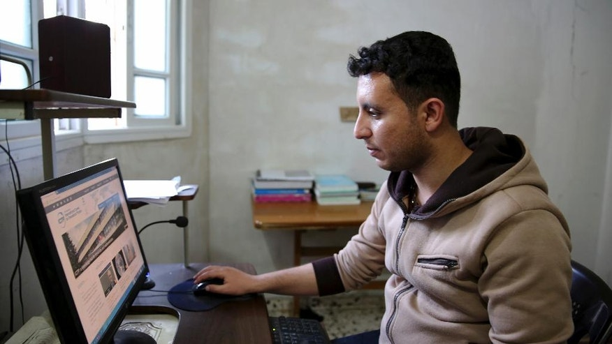 In this Tuesday, May 10, 2016 photo, Mohammed Al-Hissi, 25, looks through the internet for information about his scholarship for a Master's program in physics at the University of Triesta in Italy, at his family house in Gaza City. Gazans who have endured a border blockade by neighboring Egypt and Israel for almost a decade thought they were finally catching a break when Israel slightly eased restrictions on travel from the Hamas-ruled territory in recent months. But now Jordan appears to be emerging as an obstacle, routinely denying transit permits for Gazans and effectively preventing patients, university students and others with business abroad from leaving the coastal territory. (AP Photo/Adel Hana)