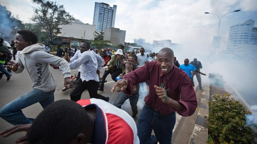 Opposition supporters, some carrying rocks, flee from clouds of tear gas fired by riot police, during a protest in downtown Nairobi, Kenya Monday, May 16, 2016. Kenyan police have tear-gassed and beaten opposition supporters during a protest demanding the disbandment of the electoral authority over alleged bias and corruption. (AP Photo/Ben Curtis)