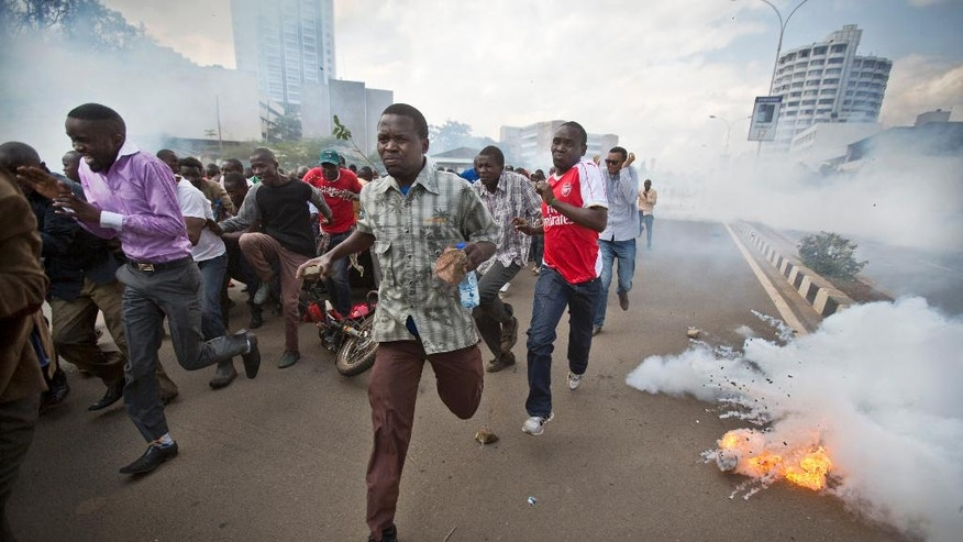 Opposition supporters, some carrying rocks, flee from exploding tear gas grenades fired by riot police, during a protest in downtown Nairobi, Kenya Monday, May 16, 2016. Kenyan police have tear-gassed and beaten opposition supporters during a protest demanding the disbandment of the electoral authority over alleged bias and corruption. (AP Photo/Ben Curtis)
