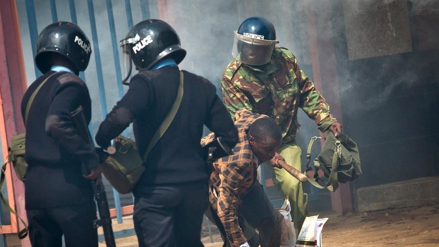 An opposition supporter is beaten with a wooden club by riot police as he tries to flee, during a protest in downtown Nairobi, Kenya Monday, May 16, 2016. Kenyan police have tear-gassed and beaten opposition supporters during a protest demanding the disbandment of the electoral authority over alleged bias and corruption. (AP Photo/Ben Curtis)