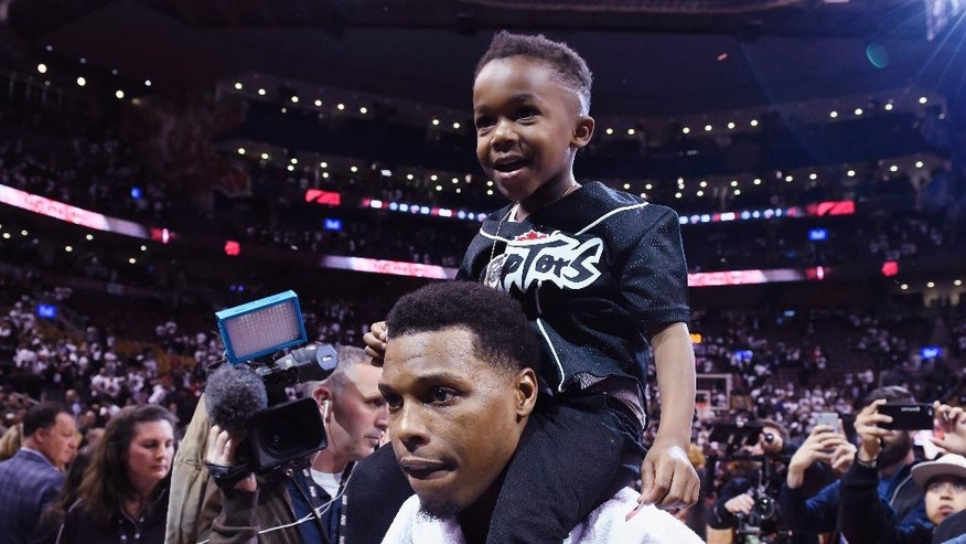 Toronto Raptors' Kyle Lowry celebrates with his son Karter following the end of the Eastern Conference semifinal NBA playoff basketball game against the Miami Heat in Toronto on Sunday, May 15, 2016. The Raptors defeated the Heat 116-89. (Frank Gunn/The Canadian Press via AP) MANDATORY CREDIT