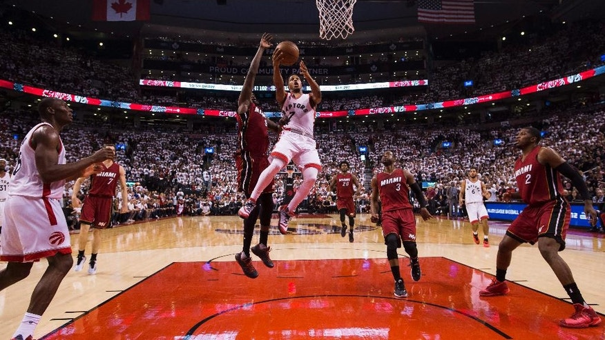Toronto Raptors' guard Kyle Lowry (7) drives past Miami Heat forward Luol Deng (9) during the second half of Game 7 of the NBA basketball Eastern Conference semifinals in Toronto, Sunday, May 15, 2016. The Raptors won 116-89. (Nathan Denette/The Canadian Press via AP) MANDATORY CREDIT