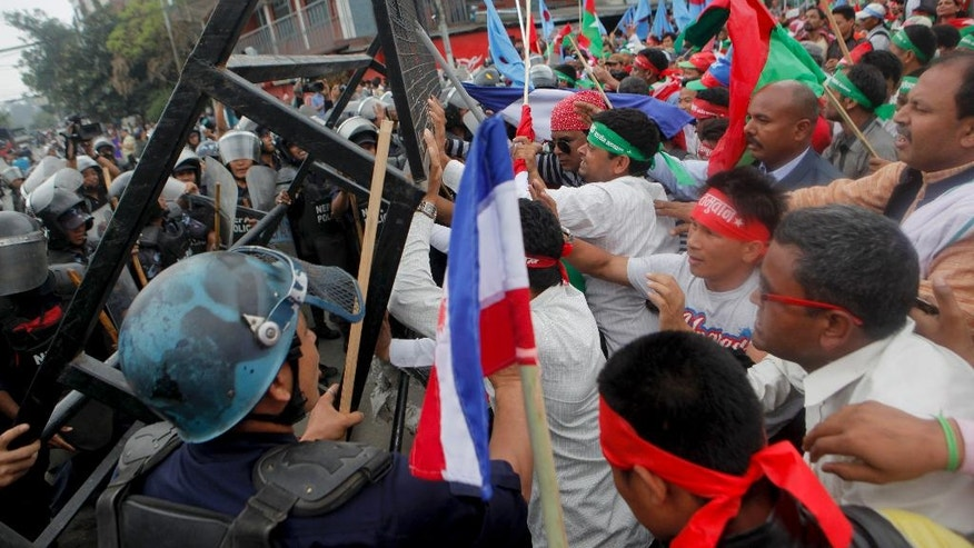 Supporters of Nepal's minority ethnic group waving their respective flags try to break through a police cordon, as they protest in a main street leading to the prime minister's office in Kathmandu, Nepal, Sunday, May 15, 2016. Hundreds of minority ethnic group supporters scuffled with police in Nepal's capital on Sunday, restarting protests against the government and the Himalayan nation's new constitution. No one was injured.(AP Photo/Niranjan Shrestha)