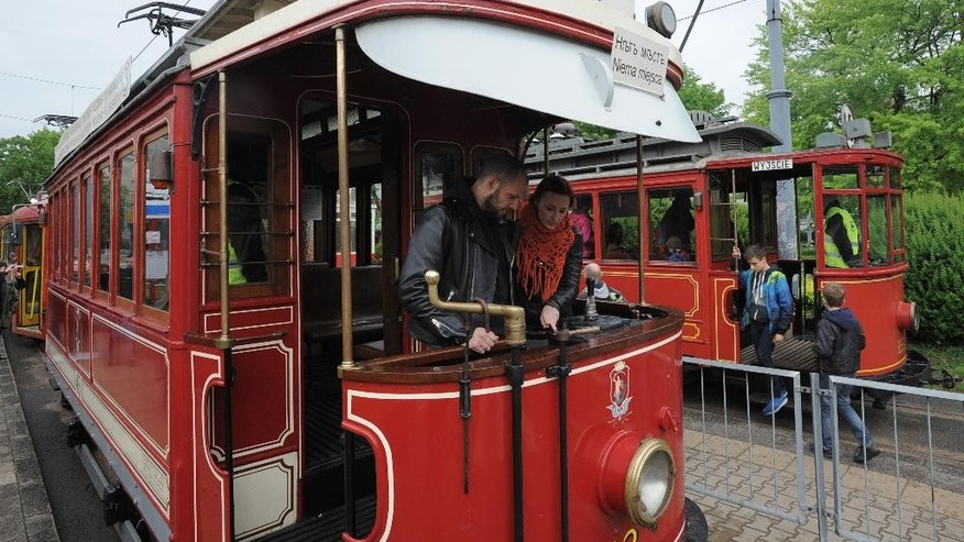 In this photo taken on Saturday, May 14, 2016 people appreciate old tramways that are once more put into service to take people in Warsaw, Poland, to and from various museums and other places of interest, during the 13th annual Night of the Museums, an increasingly popular one-night event during which many museums and offices open to the public for free, offering special activities and exhibitions, in order to widen their public. (AP Photo/Alik Keplicz)