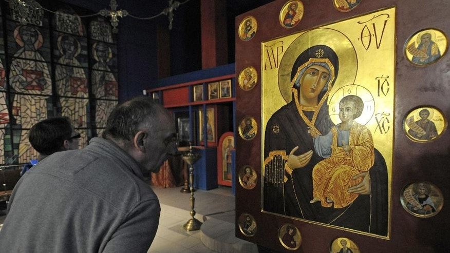 In this photo taken on Saturday, May 14, 2016 a visitor appreciates Orthodox icons at the Museum of Icons in Warsaw, Poland, during the 13th annual Night of the Museums, an increasingly popular one-night event during which many museums and offices open to the public for free, offering special activities and exhibitions, in order to widen their public. (AP Photo/Alik Keplicz)
