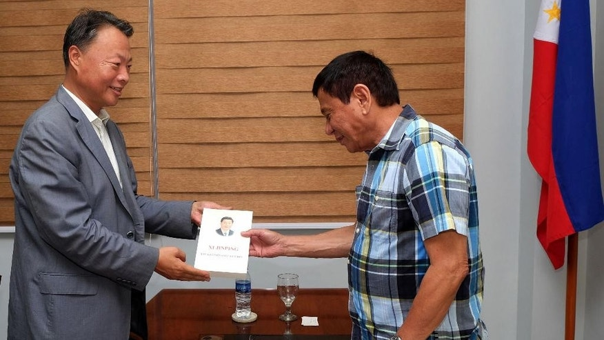 In this photo released by the Office of the City Mayor of Davao City, presumptive president-elect Rodrigo Duterte, right, receives a copy of the book on Chinese President Xi Jinping from Chinese Ambassador to the Philippines Zhao Jianhua during a courtesy call at Davao City in the southern Philippines, Monday, May 16, 2016. Presumptive Philippine President-elect Rodrigo Duterte said Monday he would offer Cabinet posts to communist rebels, a move to amend the constitution to give more power to the provinces and reimpose the death penalty in some of his first policy pronouncements since winning last week's election based on an unofficial count. (Office of the City Mayor Davao City via AP) MANDATORY CREDIT