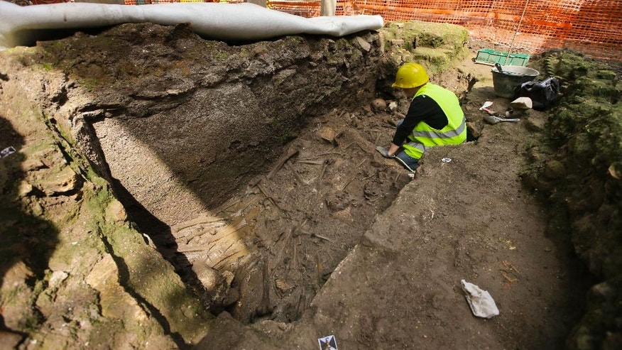 An archeologist checks ancient roman ruins discovered during work on a new underground line, in Rome, Monday, May 16, 2016. Work on the Metro C being built through the center of Rome has once again run into ancient roman ruins, this time the barracks for the Roman Praetorian guards dating back to the period of Emperor Hadrian, in the second century A.D. Officials say the barracks cover 900 square meters, and include a 100 meter hallway with 39 rooms.  (AP Photo/Alessandra Tarantino)