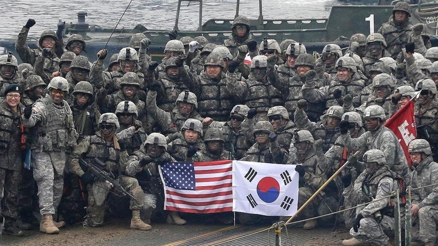 File - In this file photo taken on Dec. 10, 2015, U.S. and South Korean army soldiers pose on a floating bridge on the Hantan river during a joint military exercise against a possible attack from North Korea, in Yeoncheon, South Korea. South Korea, the United States and Japan will hold their first joint military training next month focused on cooperating to detect signs of missile launches from North Korea and trace missile trajectories, a Seoul defense official said Monday. (AP Photo/Ahn Young-joon)