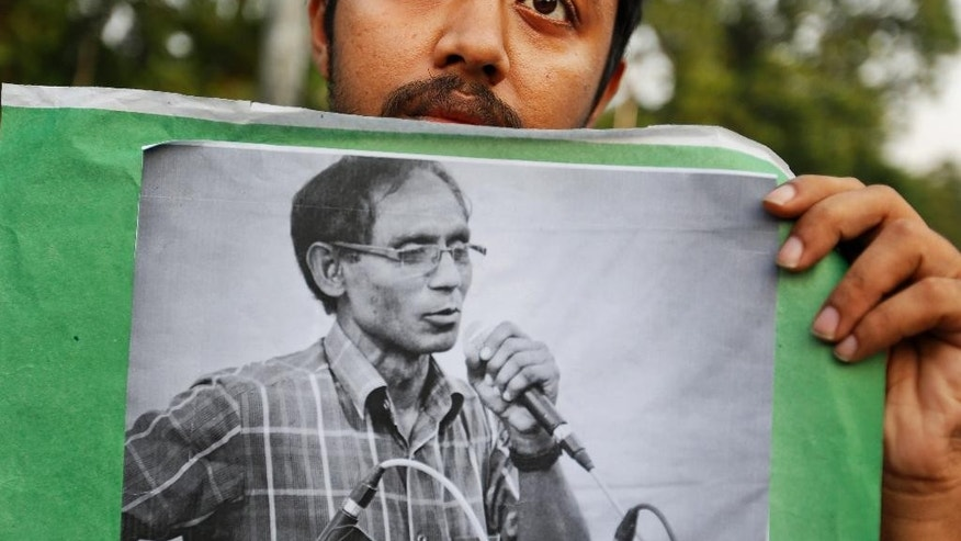 FILE- In this April 29, 2016 file photo,  a Bangladeshi student holds a portrait of a University Professor A.F.M. Rezaul Karim Siddique during a protest against his killing in Dhaka, Bangladesh. Police have arrested four members of a banned militant group, including a regional commander, suspected in the killing last month of the university professor in northwestern Bangladesh, officials said Tuesday. (AP Photo, File)