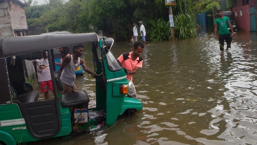 Sri Lankan men push an auto rickshaw stranded in a flooded road after heavy rains in Colombo, Sri Lanka, Monday, May 16, 2016. Flash floods caused by heavy rains have displaced hundreds of families in several parts of Sri Lanka as the Indian Ocean Island is experiencing extreme weather conditions over the last two days. (AP Photo/Eranga Jayawardena)