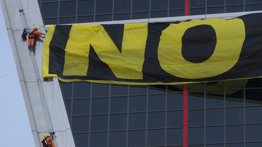 Greenpeace activists begin to hang a banner on one of the two Gate to Europe towers in Plaza de Castilla, Madrid, Spain, Tuesday, May 17, 2016. Greenpeace activists have scaled an emblematic Madrid office building to hang a banner protesting the free-trade deal being negotiated between the U.S. and the European Union. Greenpeace said the Trans-Atlantic Trade and Investment Partnership, or TTIP, threatens to undo many health, social and environmental protection measures. (AP Photo/Paul White)