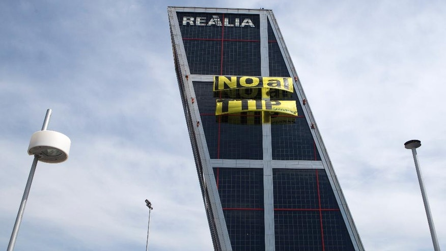 Greenpeace activists hang a banner on one of the two Gate to Europe towers in Plaza de Castilla, Madrid, Spain, Tuesday, May 17, 2016. Greenpeace activists have scaled an emblematic Madrid office building to hang a banner protesting the free-trade deal being negotiated between the U.S. and the European Union. Greenpeace said the Trans-Atlantic Trade and Investment Partnership, or TTIP, threatens to undo many health, social and environmental protection measures. (AP Photo/Paul White)