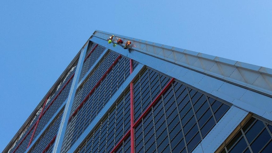 Greenpeace activists climb one of the two Gate to Europe towers in Plaza de Castilla, Madrid, Spain, Tuesday, May 17, 2016. Greenpeace activists have scaled an emblematic Madrid office building to hang a banner protesting the free-trade deal being negotiated between the U.S. and the European Union. Greenpeace said the Trans-Atlantic Trade and Investment Partnership, or TTIP, threatens to undo many health, social and environmental protection measures. (AP Photo/Paul White)