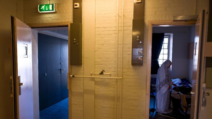 In this Wednesday, April 20, 2016 photo, Iraqi refugee Fatima Hussein, 65, prays inside her room at the former prison of De Koepel in Haarlem, Netherlands. With crime declining in the Netherlands, the country is looking at new ways to fill its prisons. (AP Photo/Muhammed Muheisen)