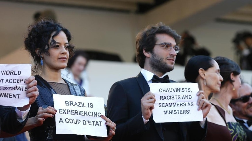 Cast from the Brazilian film Aquarius hold placards protesting against the current political landscape in Brazil after departing the screening of the film at the 69th international film festival, Cannes, southern France, Tuesday, May 17, 2016. (AP Photo/Lionel Cironneau)
