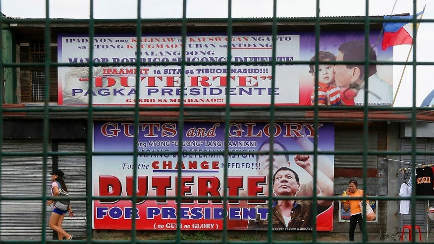 In this Wednesday, May 11, 2016 photo, residents walk past giant tarpaulins of presumptive President-elect Rodrigo Duterte at his hometown in Davao city, southern Philippines. A bold campaign promise to eradicate crimes and corruption within six months and his iron-fist approach to law and order helped catapult the longtime mayor to the presidency, but Duterte's anti-crime reputation is also a political baggage that would haunt him now as he comes under the spotlight. (AP Photo/Bullit Marquez)