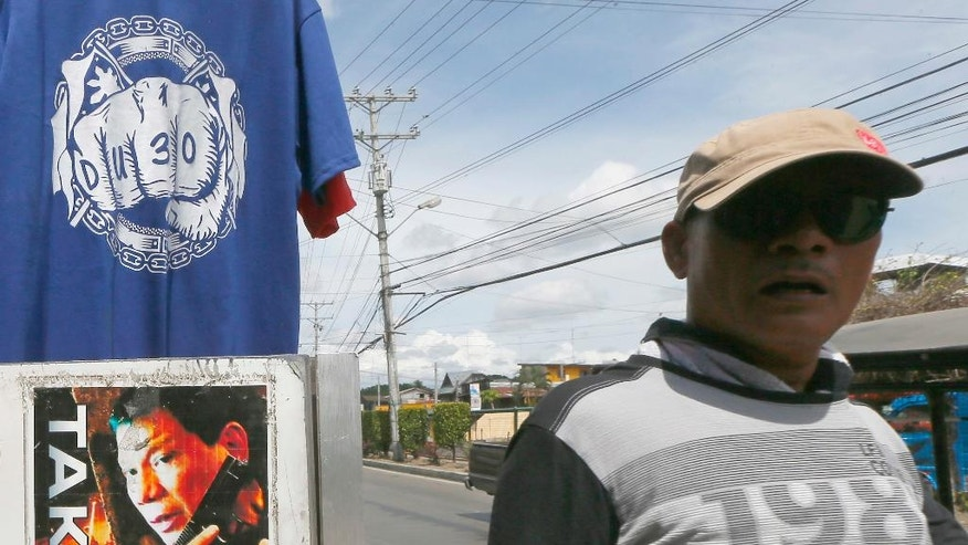 In this Wednesday, May 11, 2016 photo, a resident walks past a campaign poster of presumptive President-elect Rodrigo Duterte heralding his anti-criminality and anti-drugs platform is displayed along with souvenir T-shirts along a street at his hometown in Davao city, southern Philippines. A bold campaign promise to eradicate crimes and corruption within six months and his iron-fist approach to law and order helped catapult the longtime mayor to the presidency, but Duterte's anti-crime reputation is also a political baggage that would haunt him now as he comes under the spotlight. (AP Photo/Bullit Marquez)