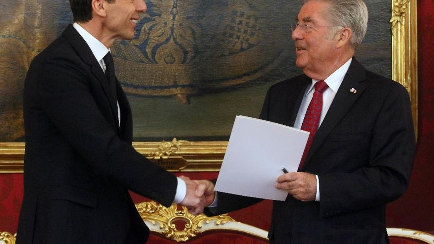 Austrian President Heinz Fischer, right, swears  in the new Chancellor Christian Kern, left, during the inauguration ceremony   at the Hofburg palace in Vienna, Austria, Tuesday, May 17, 2016. (AP Photo/Ronald Zak)