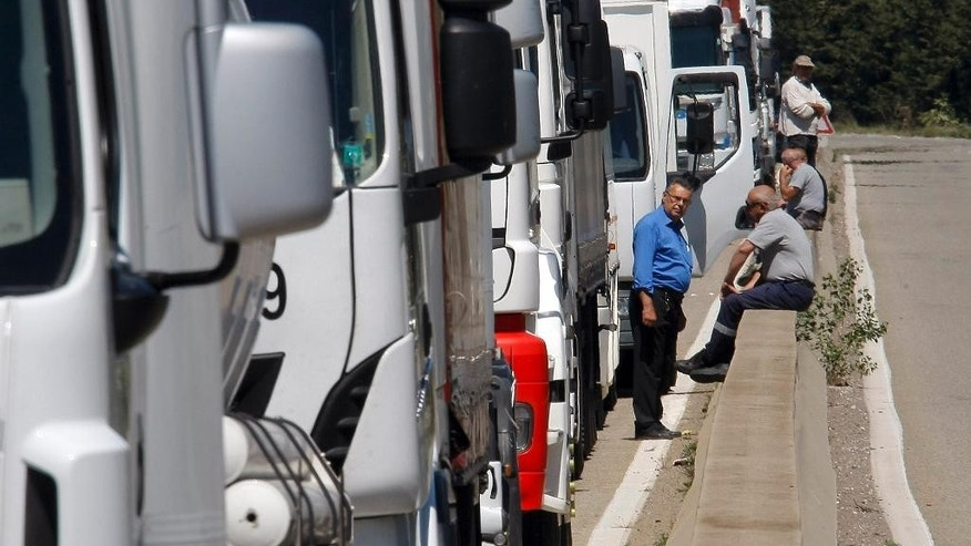 Truck drivers block the road near Fos-sur-Mer, southern France, Tuesday, May 17, 2016. Truckers are blocking highways around France to protest longer working hours in a new labor bill, but President Francois Hollande says he won't abandon the contested reform. (AP Photo/Claude Paris)