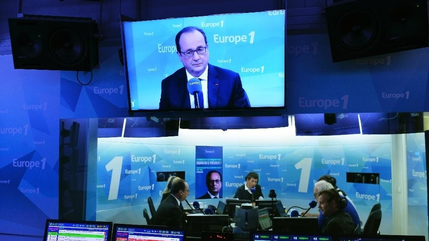 France's President Francois Hollande, left, speaks on France's Europe1 radio station, Tuesday, May 17, 2016 in Paris.  Hollande has promised he will lower taxes next year provided the state has sufficient leeway. (Miguel Medina, Pool via AP)