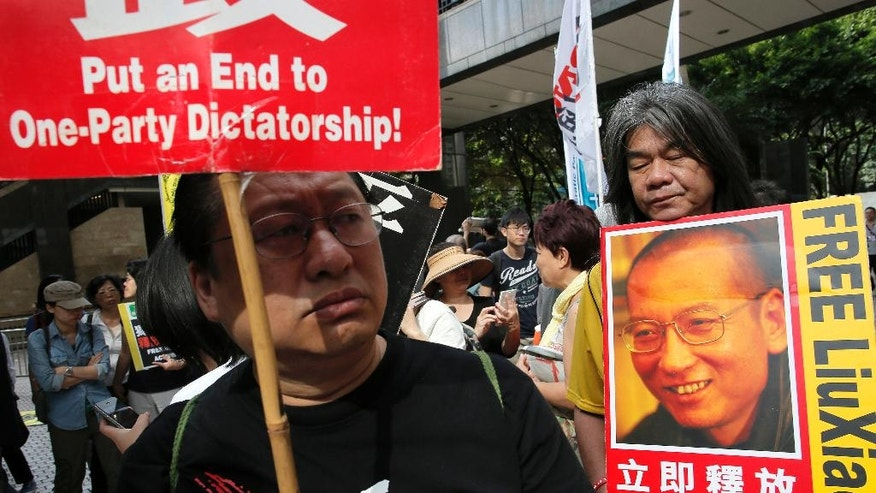 Pro-democracy activists hold placards during a protest outside the convention center where Chinese Communist Party's third-highest ranking official, Zhang Dejiang, gave a speech during a visit to Hong Kong, Wednesday, May 18, 2016.  Hong Kong authorities rolled out a massive security operation on Tuesday as they braced for protests during a top Beijing official's visit to the semiautonomous city, where tensions are rising over Chinese rule.(AP Photo/Vincent Yu)
