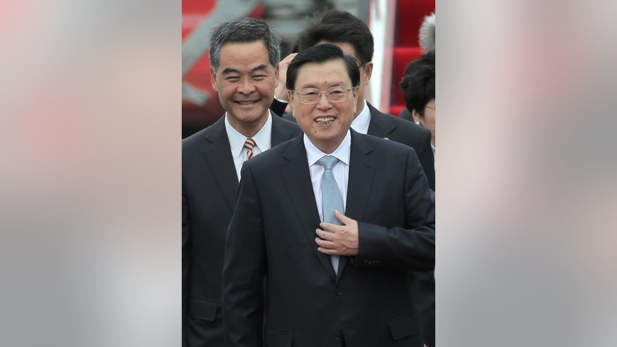 The chairman of the Standing Committee of China's National People's Congress, Zhang Dejiang, right, walks with Hong Kong's Chief Executive Leung Chun-ying after arriving at Hong Kong's airport, Tuesday, May 17, 2016. Hong Kong authorities have rolled out a massive security operation as they brace for protests during a top Beijing official's visit to the semiautonomous Chinese region. Thousands of police officers were deployed Tuesday as Zhang Dejiang began a three-day trip to Hong Kong. (AP Photo/Kin Cheung)