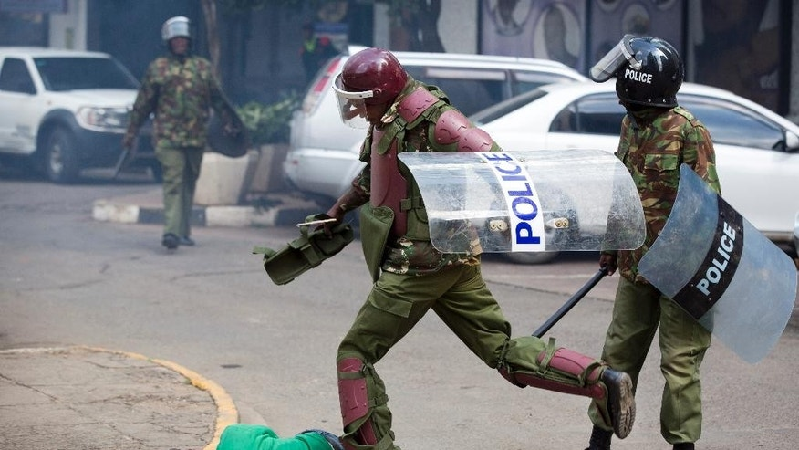 FILE - In this Monday, May 16, 2016 file photo, a Kenyan riot policeman repeatedly kicks a protester as he lies in the street after falling down while trying to flee from them, during a protest in downtown Nairobi, Kenya. In an incident that has stirred anger and condemnation across Kenya, a policeman is seen beating and kicking one protester who had fallen on a road curb, while the U.S. and human rights activists have condemned violence by Kenyan police at the opposition protest for election reforms. (AP Photo/Ben Curtis, File)