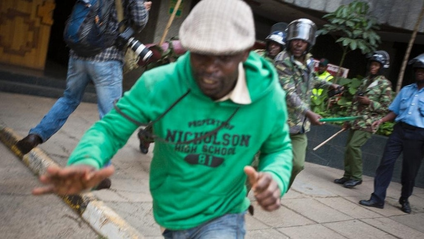 In this photo taken Monday, May 16, 2016, a protester temporarily manages to escape from riot police, before falling down and being beaten and kicked by them, during a protest in downtown Nairobi, Kenya. In an incident that has stirred anger and condemnation across Kenya, a policeman is seen beating and kicking one protester who had fallen on a road curb, while the U.S. and human rights activists have condemned violence by Kenyan police at the opposition protest for election reforms. (AP Photo/Ben Curtis)