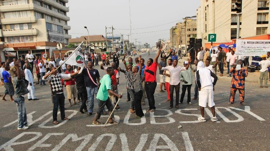 FILE- In this Friday, Jan. 13, 2012 file photo, People protest on a sign written on a major road saying' No subsidy removal'  in Lagos, Nigeria. Militant attacks on oil installations and a threatened nationwide strike are driving Nigeria's petroleum production and its naira currency to new lows. (AP Photo/Sunday Alamba, File)