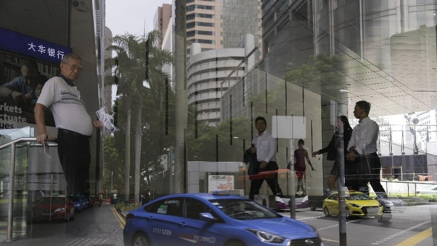 A Singapore taxi company ComfortDelGro's Hyundai taxi is reflected off the glass of an office building on Tuesday, May 17, 2016 in Singapore. Singapore's Land Transport Authority is investigating Hyundai vehicles following reports of accidents involving sudden acceleration while reversing. (AP Photo/Wong Maye-E)