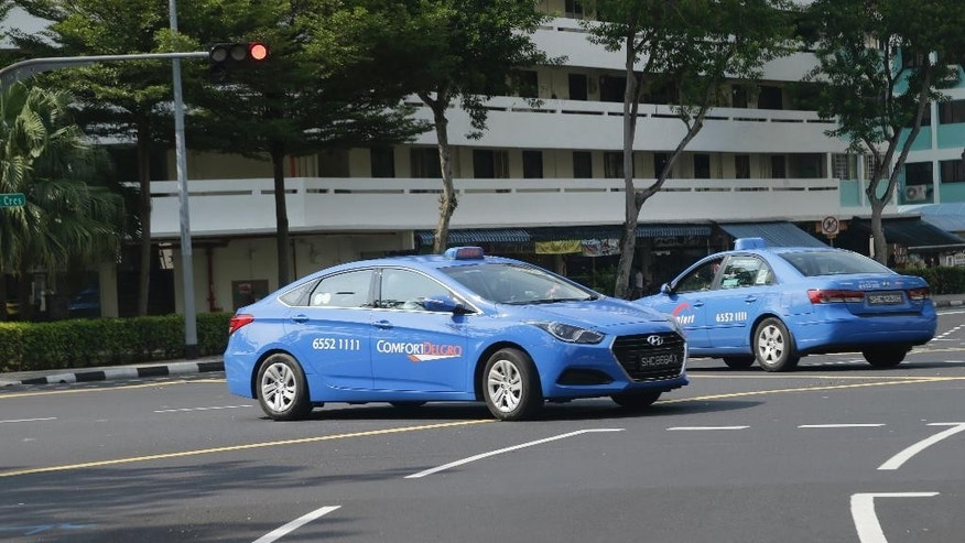Singapore company ComfortDelGro Hyundai taxis drive through a road intersection on Tuesday, May 17, 2016 in Singapore. Singapore's Land Transport Authority is investigating Hyundai vehicles following reports of accidents involving sudden acceleration while reversing. (AP Photo/Wong Maye-E)