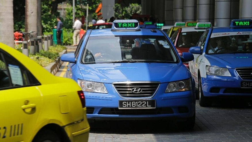 Singapore company ComfortDelGro Hyundai taxis wait in front of an office building on Tuesday, May 17, 2016 in Singapore. Singapore's Land Transport Authority is investigating Hyundai vehicles following reports of accidents involving sudden acceleration while reversing. (AP Photo/Wong Maye-E)