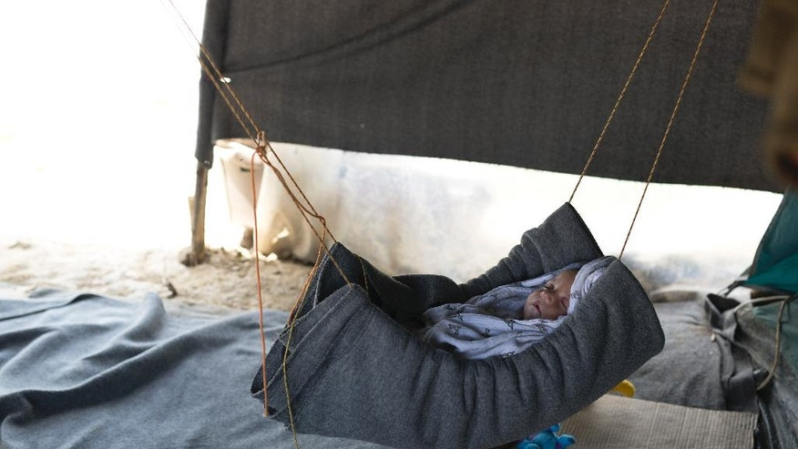 A five-month-old  Syrian baby sleeps inside a tent at a makeshift refugee camp of the northern Greek border point of Idomeni,  on Monday, May 16, 2016. Thousands of stranded refugees and migrants have camped in Idomeni for months after the border was closed. (AP Photo/Petros Giannakouris)