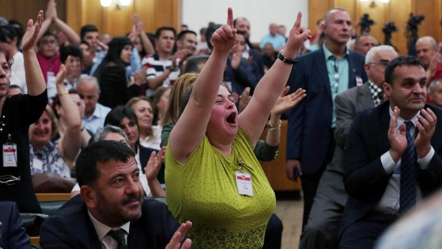 Supporters and lawmakers cheer Kemal Kilicdaroglu, the leader of opposition Republican People's Party, as he addresses at the parliament in Ankara, Turkey, Tuesday, May 17, 2016. Turkey's parliament is discussing a controversial immunity amendment, which was drafted by the ruling party after President Recep Tayyip Erdogan accused the pro-Kurdish Peoples' Democratic Party of being an arm of the outlawed Kurdish rebel group. (AP Photo/Burhan Ozbilici)