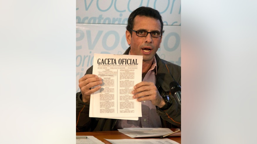 Opposition leader Henrique Capriles shows the Official Gazette government publication during a news conference at his office in Caracas, Venezuela, Tuesday, May 17, 2016, where he called for Venezuelans to ignore an economic and state of emergency decree, if put into place by Venezuela's President Nicolas Maduro, saying it's unconstitutional and a violation of international conventions and of the OAS Inter-American Democratic Charter. Maduro threatened Saturday to take over idle factories and jail their owners following a decree granting him expanded powers to act in the face of a deep economic crisis.  (AP Photo/Fernando Llano)