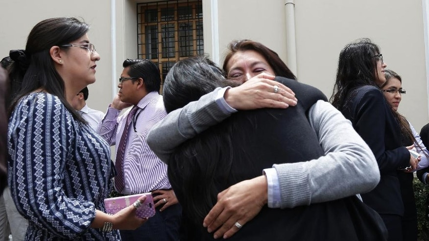 Foreign Ministry staff hug after evacuating their offices following one of two tremors felt in Quito, Ecuador, Wednesday, May 18, 2016. Both tremors were centered along the Pacific coast near the epicenter of last month's magnitude-7.8 quake and rattled homes as far away as the capital. Neither appeared to have caused serious damage. (AP Photo/Dolores Ochoa)
