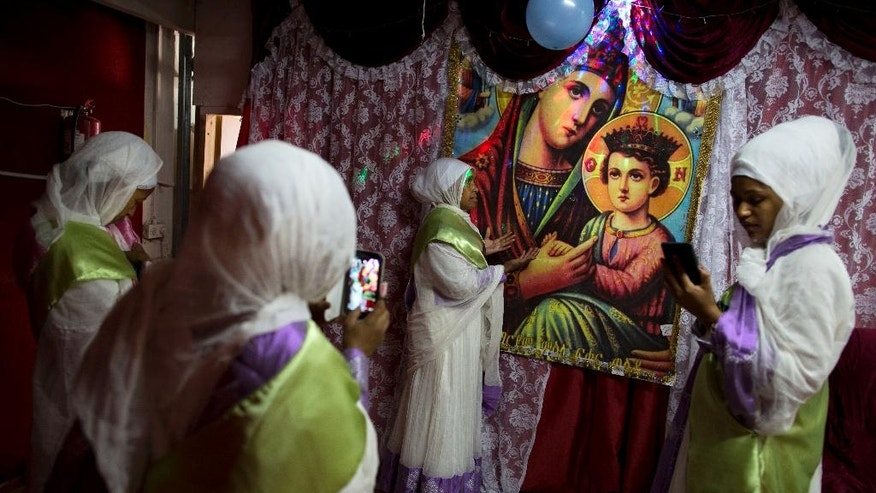 In this Saturday, May 7, 2016 photo, Members of the Eritrean Christian Orthodox migrants community take photos at a makeshift church in Tel Aviv, Israel. Hundreds of faithful gather each week in the makeshift churches. With its walls bedecked with Christian paraphernalia, it is an unlikely scene in the heart of the Jewish state, hidden in a non-descript buildings in hardscrabble south Tel Aviv. (AP Photo/Oded Balilty) **ISRAEL OUT**