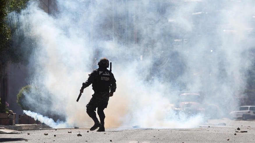 A riot police is silhouetted against a cloud of tear gas during a protest led by laid-off textile workers, in La Paz, Bolivia, Wednesday, May 18, 2016. Workers of Bolivia's largest textile company marched in protest after the government announced its closure after the failure of a state bailout plan. (AP Photo/Juan Karita)