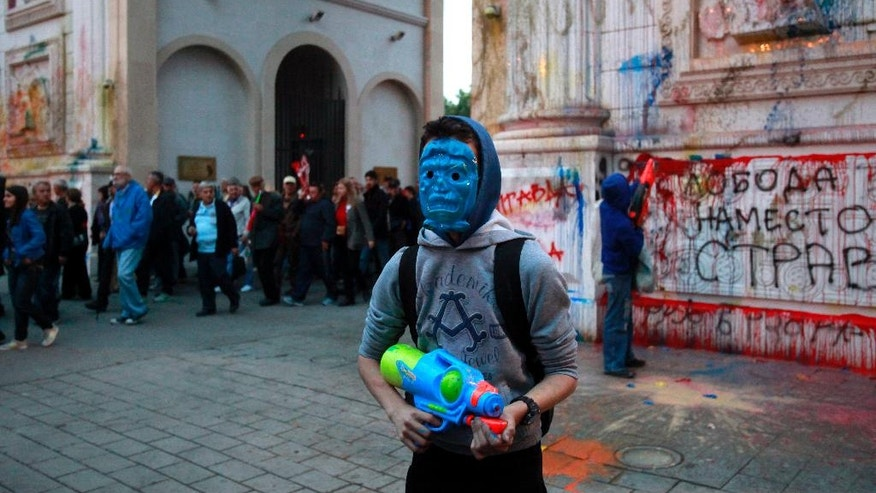 "Protestors wearing masks use water guns to spray colored paint on the triumph arc ""Porta Makedonija"", during an anti-government protest in Skopje, Macedonia, Tuesday, May 17, 2016. Protests have continued in the Balkan country almost every evening, after the country's president pardoned over a month ago dozens of politicians who were facing criminal proceedings for alleged involvement in a wiretapping scandal. The message on the right reads: ""Freedom instead of fear!"". (AP Photo/Boris Grdanoski)"
