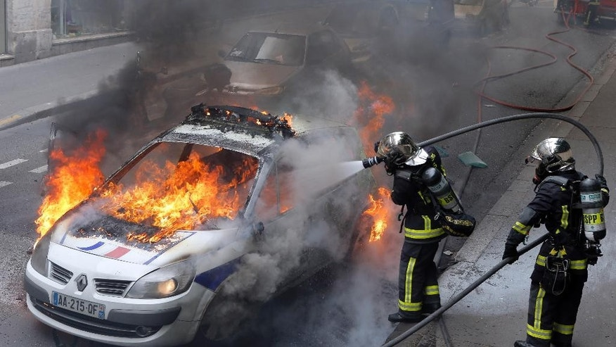 "Firefighters work on a police car set up on fire by counter demonstrators while police forces gather to denounce the almost daily violent clashes at protests against a labor reform, Wednesday, May 18, 2016 in Paris. Several hundred counter demonstrators came chanting slogans like ""everybody hates the police"" and pushing up against officers until eventually the police deployed dispersal spray. (AP Photo/Francois Mori)"